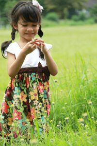 A smiling girl investigates flowers in a field